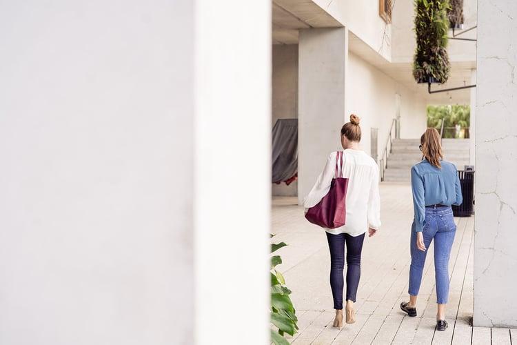 two women walking away through a hallway