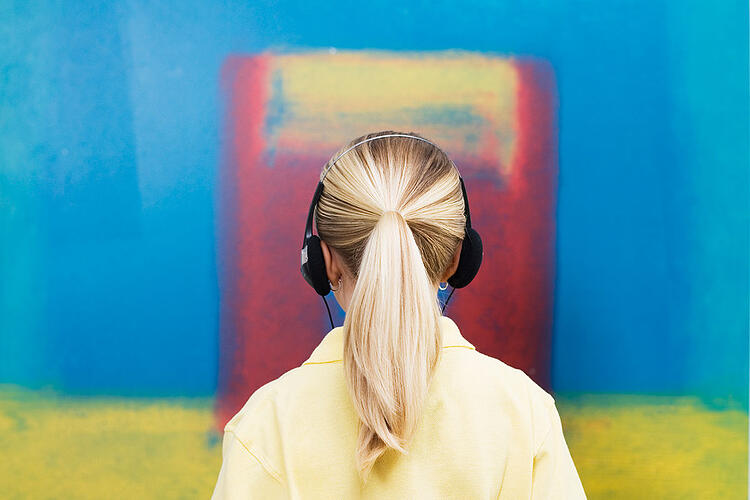 Young blonde woman with headphone in front of a colorful background