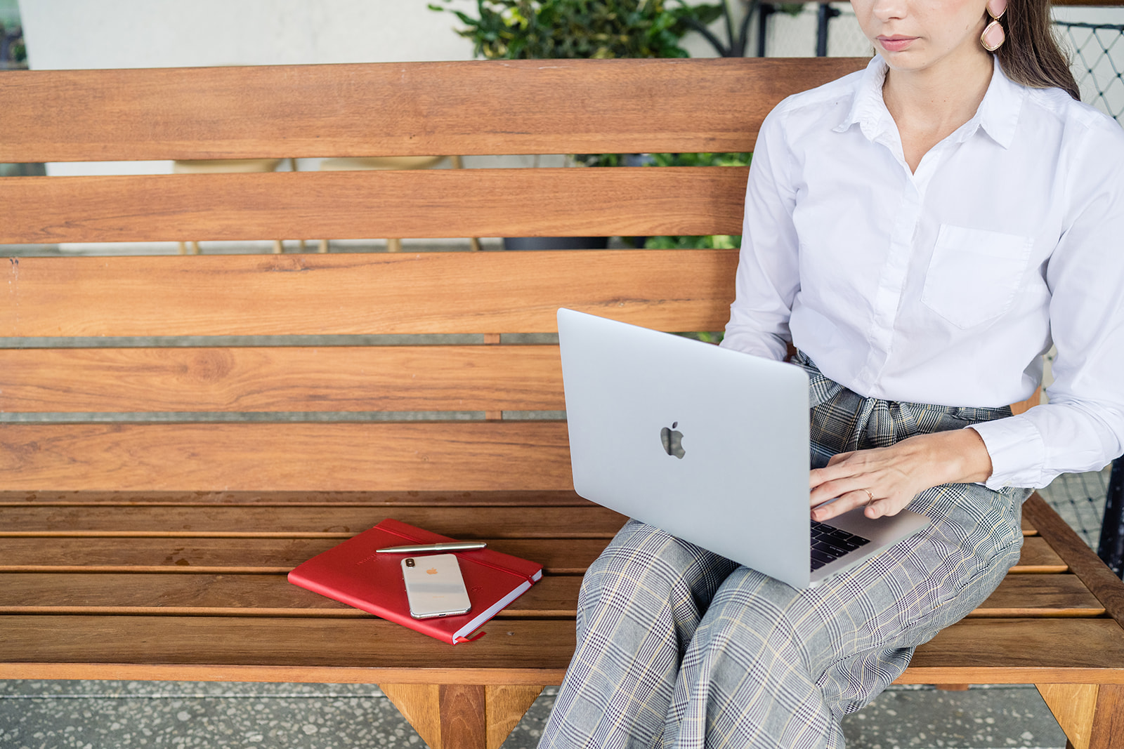 Woman sitting on bench typing on laptop
