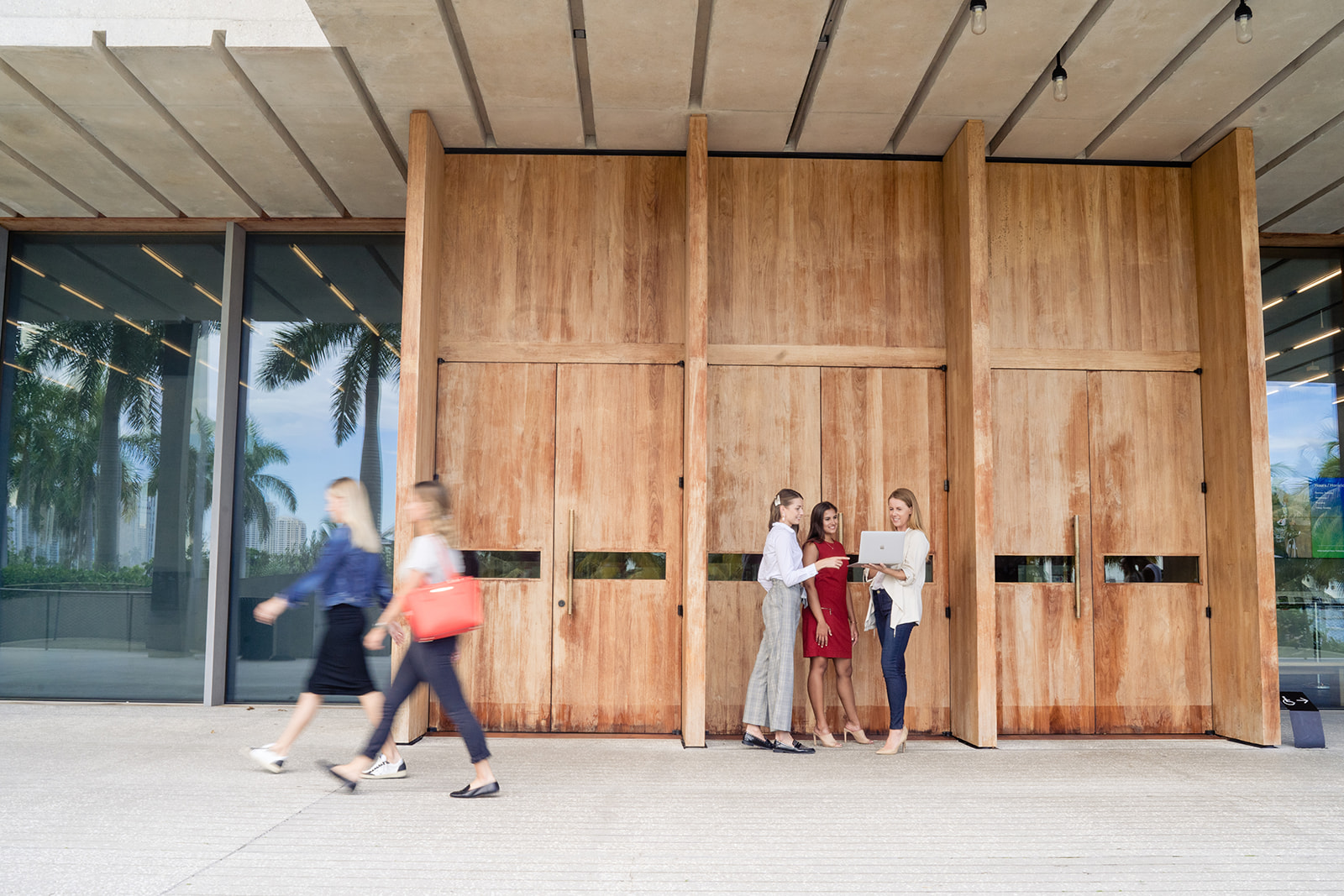 Students outside in front of a large wooden and glass structure