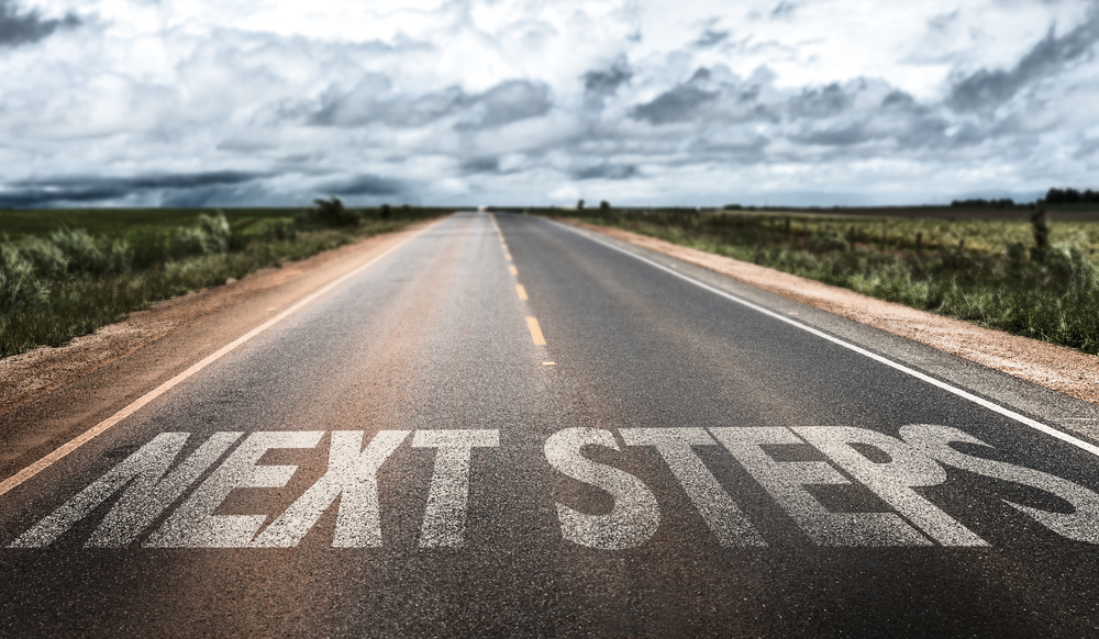 "Highway in a rural area with ""next steps"" written on the road"